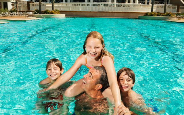 happy family in a swimming pool | Ideas for Gifts for Cancer Patients | Rock the Treatment
